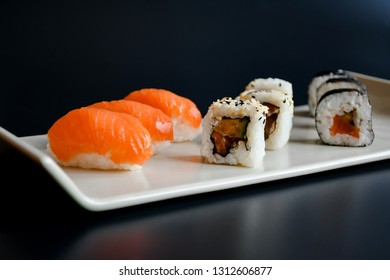 Close up top view mix sushi with various ingrediant as salmon, tuna, avocado,sesame on black background. Sushi is a deliciousJapanese dish, rice cooked with vinagre and top with fish, or vegetable .