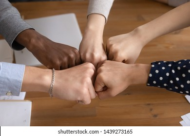 Close up top view of multicultural diverse young people give fists bump promise unity and support, multiethnic mixed group join hands involved in teambuilding activity motivated for shared success