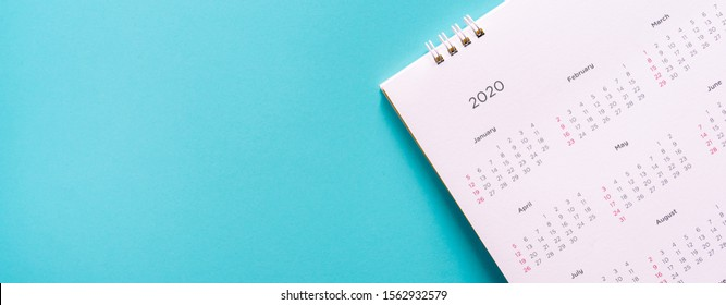 close up top view on white calendar 2020  month schedule to make appointment meeting or manage timetable each day lay on teal background for planning work and life concept