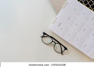 close up top view on white calendar 2020 schedule with laptop keyboard to make appointment meeting or manage timetable each day for design planning work and life concept