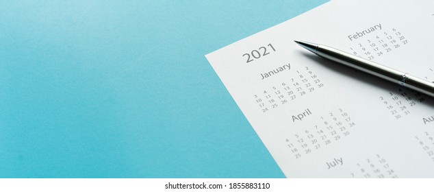 close up top view on white calendar 2021 month schedule with pen to make appointment meeting or manage timetable each day lay on teal background for planning work and life concept