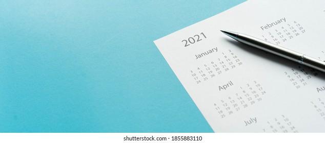 Nahaufnahme der Draufsicht über den weißen Kalender 2021 Monatsplan mit Stift für die tägliche Terminabstimmung oder Terminplanung auf Teal-Hintergrund für die Planung von Arbeit und Lebenskonzept