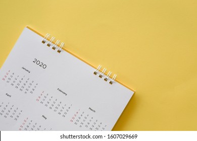 close up top view on yellow calendar 2020 month schedule to make appointment meeting or manage timetable each day lay on blue background for planning work and life concept