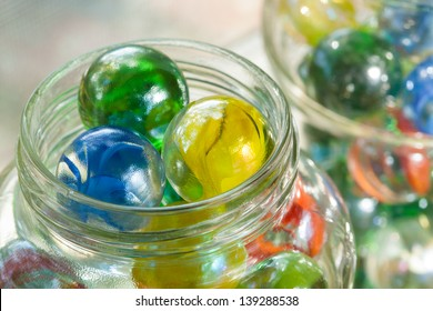 Close up top view of one inch Cat's Eye Shooter Marbles in glass mason jars