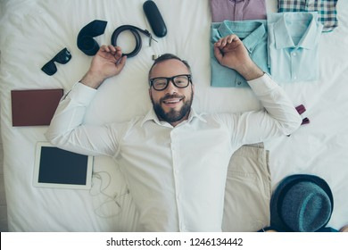 Close up top view overhead high angle photo of happily looking on camera neat handsome his him he man weared in specs and shirt lying on bed among clothes toothy smiling overjoyed with pleasure