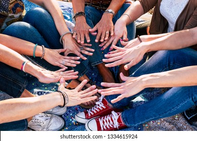 Close up top view of people putting their hands together. Friends with stack of hands showing unity and teamwork - caucasian people in friendship - hipster casual style - diversity ages