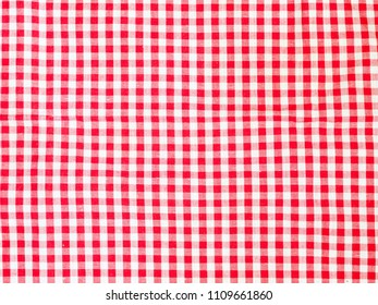 Close up top view of red and white plaid cotton picnic tablecloth. Background use