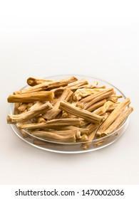 close up top view of  Shatavari,Wild Aspragus, Asparagus Racemosu   ayurvedic indian herb  sticks arranged in glass dish on white background in selective focus,