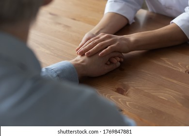 Close up top view of supportive female burse hold male patient hand at consultation in hospital, caring woman doctor support comfort caress upset man client at meeting in clinic, healthcare concept