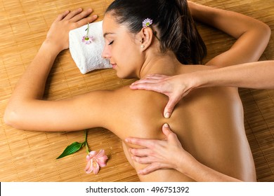 Close up top view of therapist massaging attractive woman.Young girl relaxing in low light spa atmosphere.