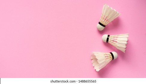 close up top view of white three shuttlecocks on pink pastel color background with copy space for design,show content and promote banner for sport concept