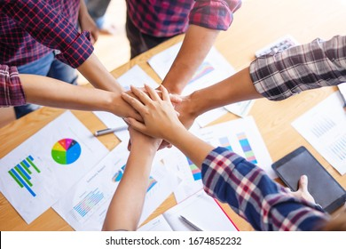 close up top view of workers putting hands together piling on top of one another representing teamwork, community help and support within the small business or company within an office environment