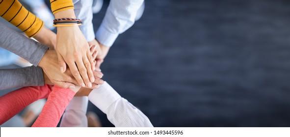 Cerrar la vista de los jóvenes empresarios que se ponen manos a la obra. Pila de manos. Concepto de unidad y trabajo en equipo.