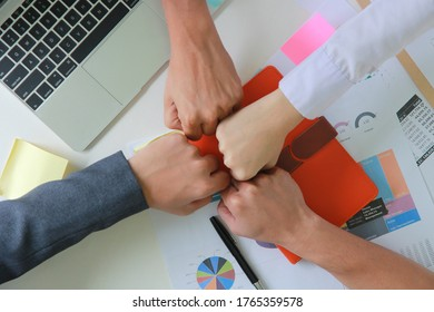 Close up  top view of young business people using fist bump (punching fists or clash of two fists) after complete a deal in the office, fist bump colleagues collaboration, teamwork concept.