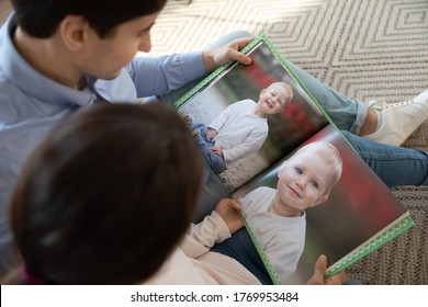Close up top view of young Caucasian couple relax at home enjoying watching childhood picture of girl child daughter, happy mom and dad look at album photos of newborn baby, family love concept