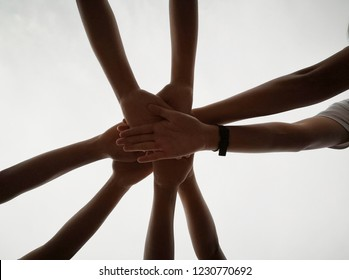Close up top view of young people putting their hands together. Friends with stack of hands showing unity and teamwork. - Shutterstock ID 1230770692