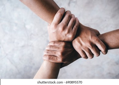 Close up top view of young people putting their hands together showing unity and teamwork.