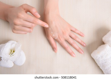 Close up top view of young woman applying cream on hand on spa table