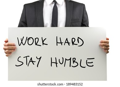Close up torso view isolated on white of a businessman in a suit holding a handwritten sign with a motivational message saying - Work Hard, Stay Humble.