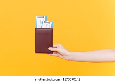 Close up tourist female horizontal hold in hand two tickets for plane with brown passport, boarding pass, isolated on yellow background. Copy space advertising area. Air flight journey concept