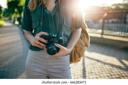 Close up of tourist photographer with retro camera. Travel photographer