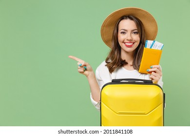 Close up tourist woman in casual clothes hat hold passport tickets yellow suitcase point finger aside workspace isolated on green background Passenger travel abroad weekend getaway Air flight concept. - Shutterstock ID 2011841108