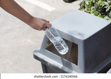 Close up of a Tourist woman hand throwing garbage in a trash bin on the street