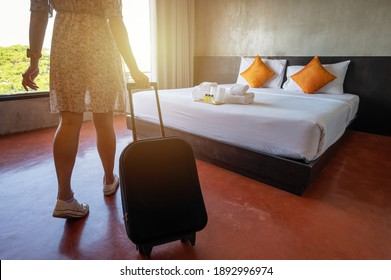 Close up of tourist woman pulling her luggage in hotel bedroom after check-in. Conceptual of travel and vacation.