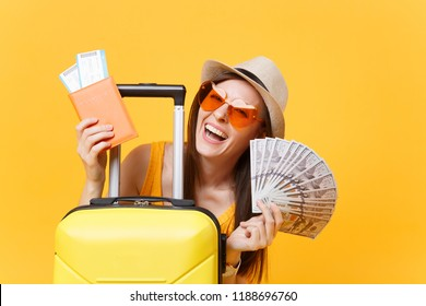 Close up tourist woman in summer casual clothes, hat at suitcase passport cash money isolated on yellow background. Passenger traveling abroad to travel on weekends getaway. Air flight concept