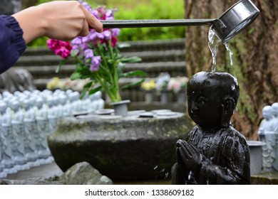 Close up tourist woman worshiping of Jizo Statue pouring water on Jizo's head with a ladle. Hase-dera Temple in Kamakura.
