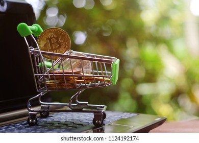 close up toy shopping cart with bitcoin on notebook, saving money for future, ethereum cryptocurrency, blockchain business technology concept