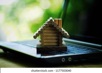 close up toy wood house on computer, green nature background, saving money for future, manage to success, property business technology concept