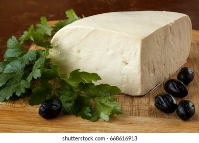 Close up of a traditional bulgarian fresh unripened cottage cheese from cow's milk on a rustic wooden cutting board, decorated with olives and parsley