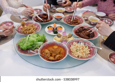 Close Up Of Traditional Chinese Food With People Using Chopsticks As Background Soft Focus