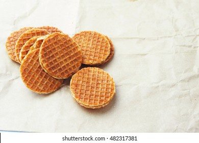 Close up of a traditional Dutch caramel waffle on a waxed paper.