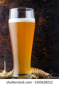 Close - up of traditional full glass of unfiltered wheat beer on brown old dark background