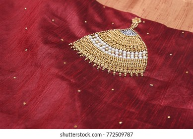Close up of traditional handmade, red and black  Indian Jhumka designer silk , jute  sari or saree with golden details, beads and stones. woman wear on Onam festival, Vishu, wedding in Kerala India.