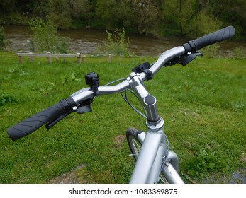 close up of traditional looking silver bike handlebars with a view to the field and river