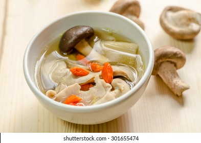Close up Traditional oriental pork broth with shiitake mushrooms on wooden table