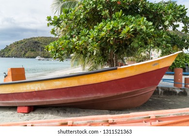 Close up of a traditional red & yellow yole fisherman small boat, in the sea sand under a tropical green tree, with blue sky, hill, in Caribbean beach of Sainte Luce, Martinique, Antilles, West Indies