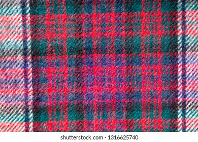 Close up of traditional Scottish woolen tartan fabric. Checkered cashmere plaid.