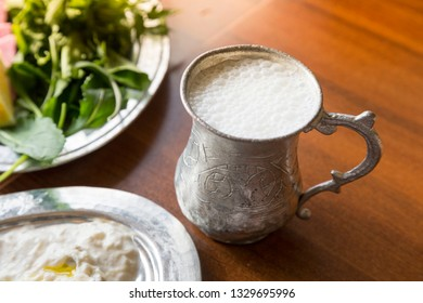 Close up Traditional Turkish beverage Ayran made with yoghurt and water in metal vintage old glass cup on wood table background.