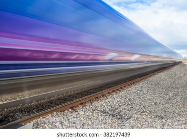 Close up of train speeding through English countryside on bright sunny day with extended exposure for extended   motion blur