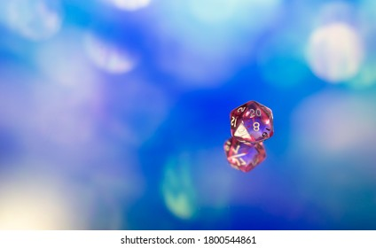 Close up of a transparent polyhedral dice on a blue reflective surface.