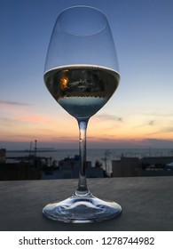 Close up of a transparent wine glass, with black & white liquid due to sunset light, put on a wall with a view on a Mediterranean city & sea and blue, yellow and orange colored sky, at the happy hour.