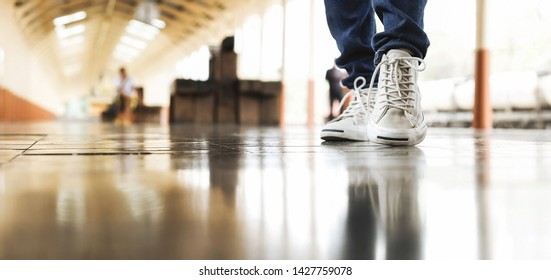 Close up of traveler legs with white shoes walking at train station. Travel concept.