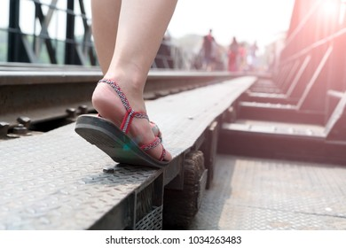 close up of the traveler sneakers shoe while walking on the sunny day at the railway bridge