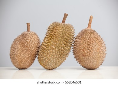 Close up of tree durians over gray background.