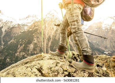 Close up of trekking legs and boots on french alps - Hiker with backpacks and sticks walking on mountain - Wanderlust travel concept with sporty people at excursion in wild nature - Focus on left shoe