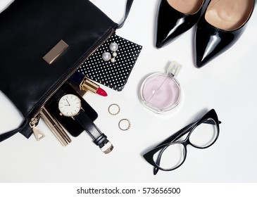 Close up trendy accessories for young woman. Overhead black bag and lacquered black shoes